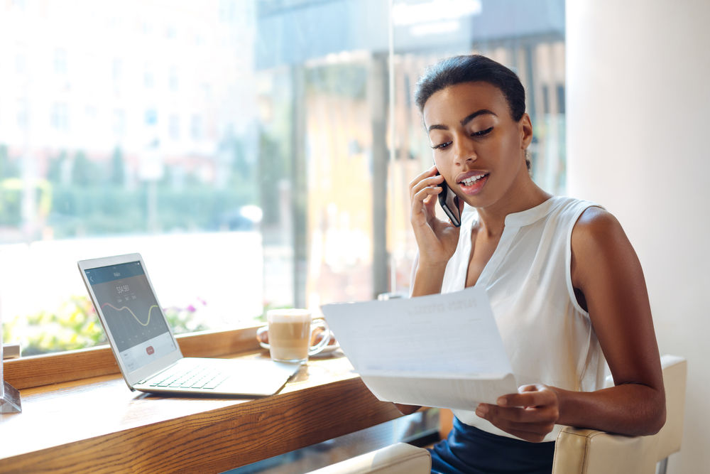 picture of woman on the phone with laptop and looking at looking at paper