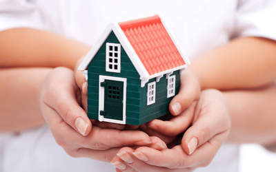 hands holding a small wooden house