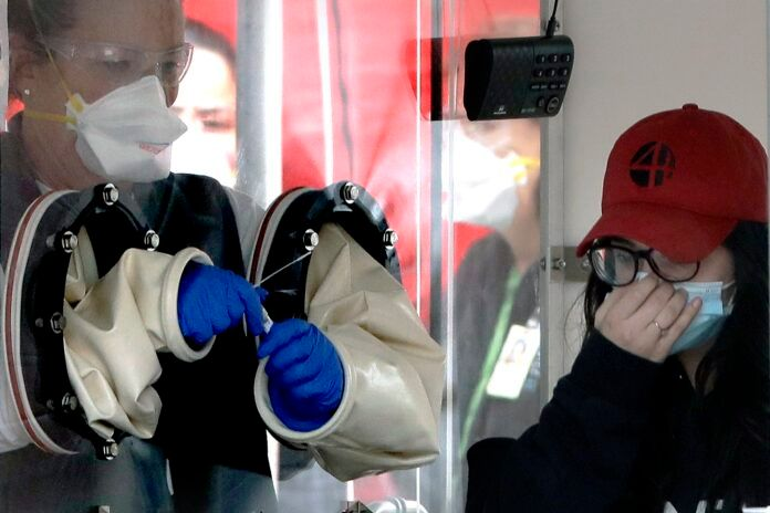 DEATHS FROM COVID-19 are expected to surpass 2,000 this week in Massachusetts. Above, a woman positions her mask after a medical worker, left, took a sample from her nose at a coronavirus testing tent outside MGH Healthcare Center. AP FILE PHOTO/STEVEN SENNE