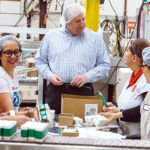 HELP WANTED: Bradford Soap Works Inc. in West Warwick is one of numerous Rhode Island companies hiring even though the economy has hit the skids during the coronavirus pandemic. In this 2018 file photo, CEO and President Stuart Benton works on the packing floor with Bradford employees. / PBN FILE PHOTO/RUPERT WHITELEY