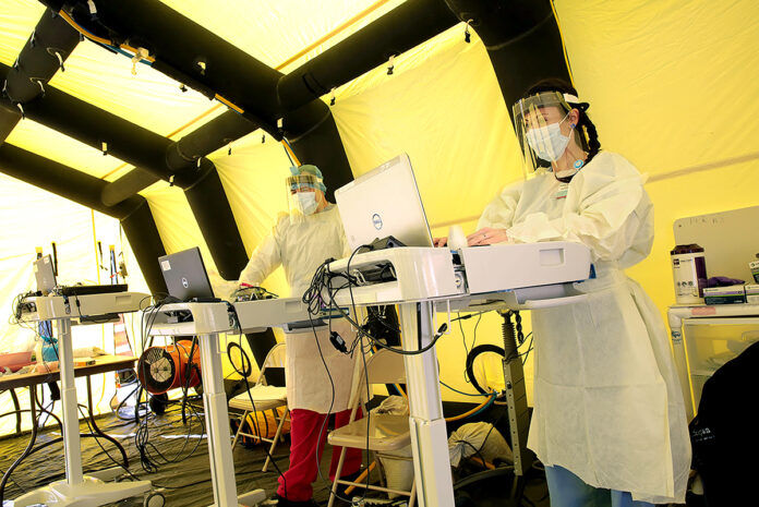 PREPARED: Health workers type on laptops inside the incoming COVID-19 patient tent set up outside the Emergency Department at Rhode Island Hospital in Providence.  COURTESY LIFESPAN CORP.