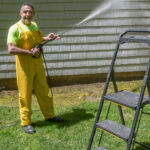 ONE-MAN GAME: David Rothenberg, owner of A Plus Handyman Services LLC, power-washes a house. The one-man operation offers a range of services, including painting, siding, excavating and sheet-rock installations. / PBN PHOTO/MICHAEL SALERNO