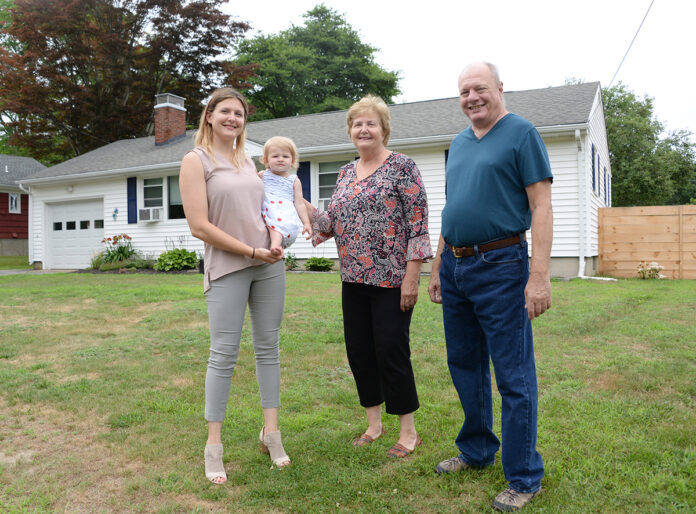 NEW HOME: Nicole Tickner with her daughter Lily, and parents George and Judy Vit. They are in front of the South Kingstown house that Tickner bought for them after they moved to Rhode Island to be closer to their granddaughter. / PBN PHOTO/ELIZABETH GRAHAM