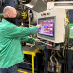 DOING HIS DUTY: Bill Burton, extruder team lead and U.S. Army veteran, operates an extrusion line on the Cooley manufacturing floor using a recently installed proprietary touch-screen technology. / COURTESY COOLEY GROUP