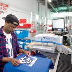 HEATING UP: SquadLocker machine operator Daudi Nabaasa applies a logo to a jersey at a heat-transfer machine at the Warwick company. / PBN PHOTO/DAVE HANSEN