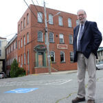 NEW LIFE: Joseph Garlick, executive director of NeighborWorks Blackstone River Valley, outside one of the downtown Woonsocket mill buildings that the organization is converting into live-work space for artists and businesses. / PBN PHOTO/ELIZABETH GRAHAM