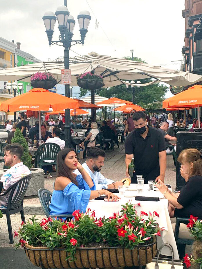 """SAFETY FIRST: A waiter serves diners during an """"Al Fresco on the Hill"""" event on Atwells Avenue in Providence. Restaurateurs say stressed staffers are playing the role of enforcers of mask guidelines while keeping an eye out for state inspectors.  / COURTESY FEDERAL HILL COMMERCE ASSOCIATION"""