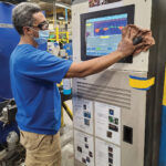 MR. CLEAN: Ben Pereira, extruder team leader, disinfects his extrusion touch screen at Cooley Group's Pawtucket factory. / COURTESY COOLEY GROUP