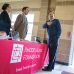 LEADING THE WAY: Rhode Island Foundation CEO and President Neil D. Steinberg, right, works with staffers at an expo event.COURTESY RHODE ISLAND FOUNDATION