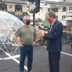 """WEATHER OR NOT: Lt. Gov. Daniel J. McKee gets a closer look at an """"igloo"""" set up at Kay's Restaurant in Woonsocket. With McKee is Kay's owner David Lahousse. Ten of the structures, which cost over $1,400 each, are now in place at the restaurant to extend outdoor dining. / COURTESY OFFICE OF LIEUTENANT GOVERNOR"""