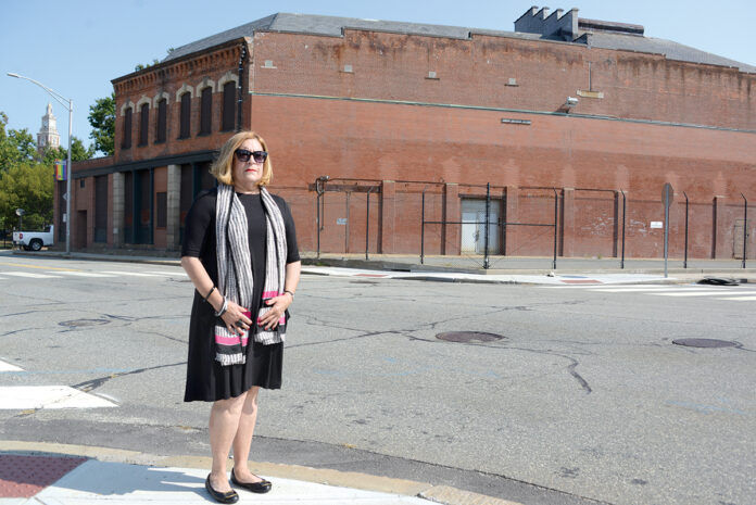 PARK CONCERNS: Sharon Steele, president of the Jewelry District Association, stands in front of the proposed site for the Dyer Street bus hub. She's an opponent of the Providence Multi-Hub Bus System, in part because she believes that people waiting for buses at the Dyer Street hub would spill into the nearby waterfront park, diminishing the park's intended use. / PBN PHOTO/ELIZABETH GRAHAM