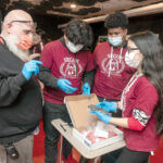 HELPING STUDENTS: Angelo Garcia, founder and head of school at Segue Institute for Learning in Central Falls, with eighth graders, from left: Marvin Gonzalez, Christian Beaton and Kimberly Ortega. / PBN PHOTO/MICHAEL SALERNO