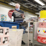 SIGNS OF THE TIMES: National Marker Co., creator of safety identification signs and products, increased its sales by more than 25% in 2020, as its products were in high demand during the COVID-19 pandemic. At right, manufacturing technician Tim Egan looks over some signs. / PBN PHOTO/RUPERT WHITELEY
