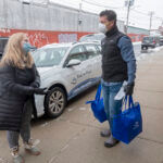 LOADING UP: Meg Grady, executive director for Meals on Wheels of Rhode Island, and volunteer Ted Fischer, CEO of Ageless Innovation, help load food into vehicles for some deliveries. Grady said the organization's home-delivery program saw a 7% increase in seniors served and a 9% increase in meals served in 2020 compared with 2019. / PBN PHOTO/MICHAEL SALERNO