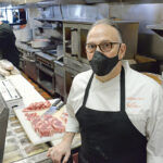 HUNGRY FOR HELP: Anthony Tarro, co-owner of Siena restaurant, says the business has struggled to find workers recently. In the background, sous chef Michael Lynch assists Tarro in the kitchen of Siena's East Greenwich location. / PBN PHOTO/ELIZABETH GRAHAM