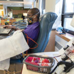 IN NEED: Andre Gill donates blood at the Rhode Island Blood Center. The center says donations are decreasing as people become more active as the economy reopens and COVID-19 infections decline. / PBN PHOTO/RUPERT WHITELEY
