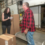 ALL-IN: Christine Soave Crum, left, owner of Gentry Moving and Storage in Cranston, accepts a delivery of office furniture from Don Erickson of Aspen Transport Service. Crum worked full time as a teacher when she founded the moving company with a partner in 2005 but now focuses all of her attention on Gentry.  / PBN FILE PHOTO/MICHAEL SALERNO