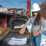 HANDS-ON: Stephanie Robat, owner of FR Engineering Group Inc., prepares to examine a core sample brought up by a drill rig on a work site in Warwick. / PBN FILE PHOTO/MICHAEL SALERNO