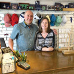 AT THEIR POST: John and Sarah Cullen behind the counter of their gift shop Solstice on Water Street on Block Island. They're hoping for a very busy summer. / PBN PHOTO/CASSIUS SHUMAN