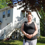 DOUBLE DUTY: Virginia Burdick, a certified nursing assistant and mother of two, stands in front of her two-bedroom apartment in South Kingstown. Burdick, who works two jobs to be able to afford the rent for the apartment, was recently approved by the South County Habitat for Humanity for one of its homes in Exeter, which she hopes to move into by the end of the year. / PBN PHOTO/ELIZABETH GRAHAM