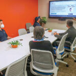 WORKING TOGETHER: Employees at Secure Future Tech Solutions collaborate with one another inside the company's conference room. / COURTESY SECURE FUTURE TECH SOLUTIONS