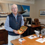 TRAVEL COMPANION: Paul Fleming is the owner of marketing communications firm Fleming and Co. in Newport. The firm also designs and sells products, including the Flight Companion that Fleming is holding, which is a kit he designed for people who travel infrequently and don't have an established packing routine for carry-on items. / PBN PHOTO/TRACY JENKINS