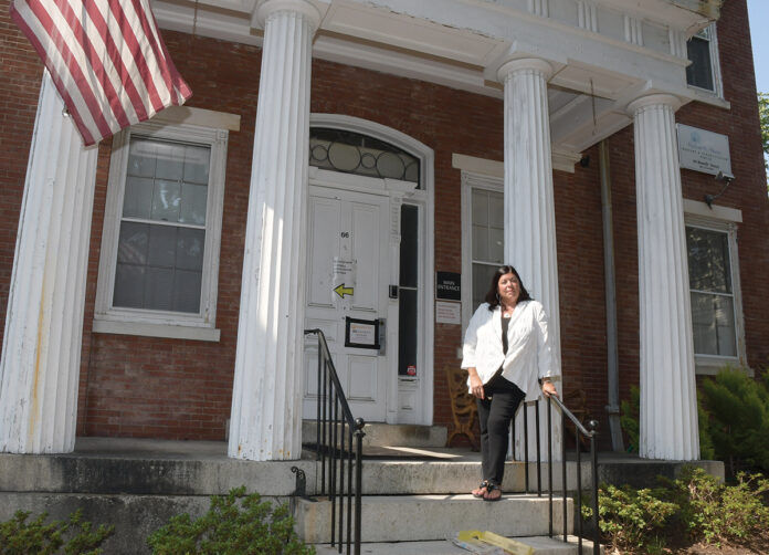 COVID CASUALTY: Stephanie lgoe stands in front of the former Hallworth House building in Providence, a nonprofit nursing home where she served as administrator before it closed in the summer of 2020 due to the COVID-19 pandemic. / PBN PHOTO/MIKE SKORSKI