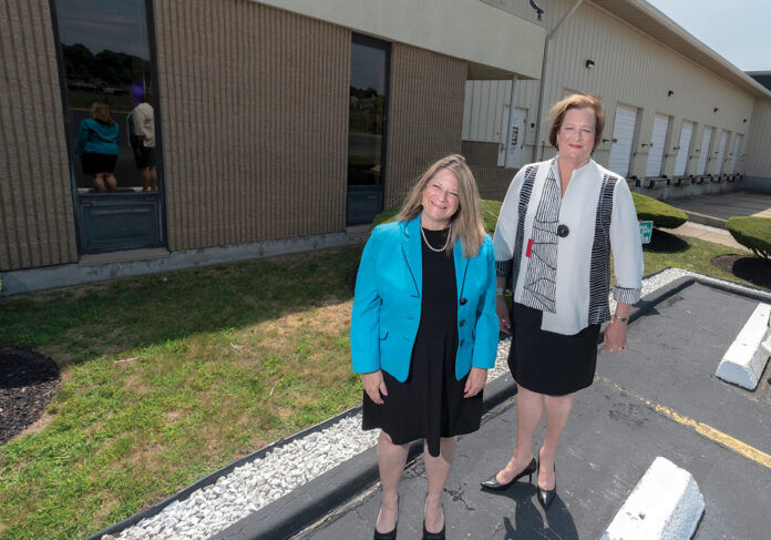 TRAINING HUB: Jennifer Menard, left, interim vice president of economic and business development at Bristol Community College, and Laura Douglas, college president, stand outside the future home of the school's National Offshore Wind Institute on the New Bedford waterfront. / PBN PHOTO/MICHAEL SALERNO