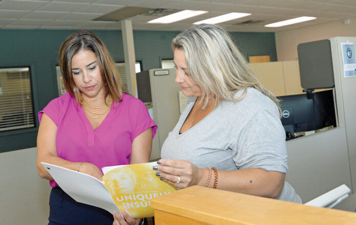 POLICY PERUSAL: Mary Caruso, left, director of business development at Carey, Richmond & Viking Insurance Agency in Middletown, talks with CaraMarie Costa, personal insurance account manager. / PBN PHOTO/ELIZABETH GRAHAM