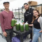MAJOR GROWTH: From left, juicing company Fully Rooted Inc. co-owners Benjamin Aalvik, Angelo Mollis and Amanda Repose in their production space in Pawtucket. Although the retail store had to close and farmers market sales were cut in half during the COVID-19 pandemic, delivery across Rhode Island and Massachusetts grew exponentially. / PBN PHOTO/ELIZABETH GRAHAM