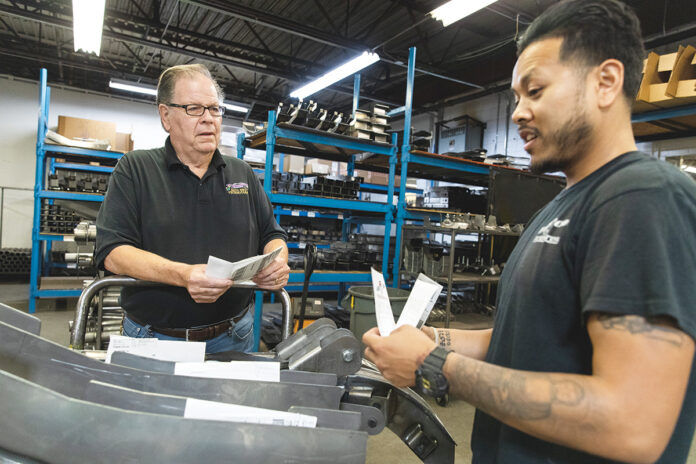 EXPANSION PLANS: Gerald Carlson, left, owner of Auto Rust Technicians in Cranston, recently spent $500,000 to expand operations and is considering buying more equipment. He's pictured with manufacturing manager Karr Thang.  / PBN FILE PHOTO/RUPERT WHITELEY