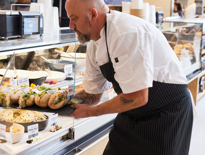 REPLENISHING SUPPLIES: Executive chef Todd Schiller places sandwiches in a display case at FoodLove specialty market in Middletown. / COURTESY FOODLOVE/KRISTIN TEIG