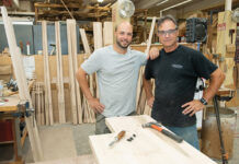 """GROWING STAFF: Scott J. Pacheco, left, owner and president of Scott James Furniture & Design in Tiverton, with his father, Rob Pacheco, head bed builder. Although the company shut down for two months at the start of the pandemic in March 2020, it has done well since then, Scott Pacheco said, especially """"doing a lot more work in the wealthier coastal neighborhoods for people leaving New York,"""" which has resulted in more full-time employees now than before COVID-19 hit. / PBN PHOTO/DAVE HANSEN"""