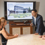 SNEAK PEEK: Windmoeller & Hoelscher Corp. Senior Vice President Javeed Buch, standing, meets with staffers at the firm's North American headquarters in Lincoln. On the screen is an artist's rendering of the company's future offices that are soon to be under construction. / PBN PHOTO/DAVE HANSEN