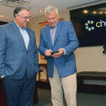 AFFORDABLE ACCESS: Blaine Carroll, right, president of First Circle Inc., shows Joseph Perroni, CEO of Delta Dental of Rhode Island, the Chewsi app, which was launched in 2017 by First Circle, a subsidiary of Delta Dental. / PBN PHOTO/ELIZABETH GRAHAM