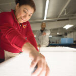 BRILLIANT JOB: Lumetta Inc. employees Mirna DeLaCruz, in the foreground, and Yonfi Polanco work at a light table in the manufacturer's facilities in Warwick.  / COURTESY LUMETTA INC.