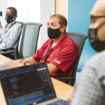 LOOKING BRIGHT-EYED: Members of Gilbane Building Co.'s application development team gather for a meeting at the company's headquarters in Providence. From left are Gevin Odhiambo, Brian Prosnitz and Peter Mahon. / PBN PHOTO/RUPERT WHITELEY