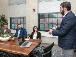 STEADY GROWTH: Cole DeSanty, right, director of client development for The Hire LLC, speaks with his colleagues, from left, CEO Tyler Wentworth; Bryan Soderberg, manager of candidate success; and Chief Operating Officer Erin Pavane. The Providence job placement firm has seen steady revenue growth since offering unlimited PTO from its inception in 2017. / PBN PHOTO/MICHAEL SALERNO