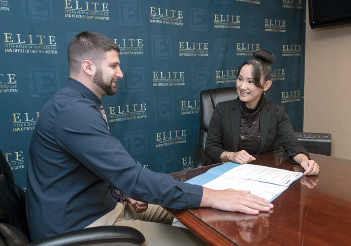 TITLE TALK: Diep Nguyen, right, managing member of Elite Title & Closing Services LLC in East Providence, meets with Robert Watson, associate attorney. / PBN PHOTO/MICHAEL SALERNO
