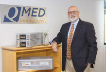 KEEPING TABS: Victor Nunes, founder and principal owner of QMed Innovations Inc. in Middletown, showcases the company's Quest tracking product, which uses internet-connected technology to provide location data so manufacturers can keep track of their surgical kits that are used in orthopedic procedures. / PBN PHOTO/KATE WHITNEY LUCEY