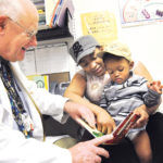 COMMUNITY SPIRIT: Dr. John Moran with 1-year-old Giovani Andrade and his mother, Kim Andrade, at the Allen Berry Health Center. /