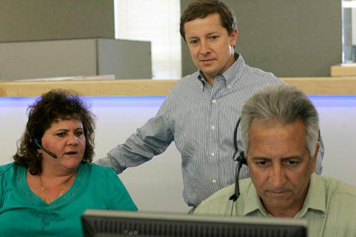 PREMIUM SERVICE: InsureMyTrip.com President and CEO Jim Grace looks on as sales representative Nancie Sanita trains new hire Rick Ventriglia. /