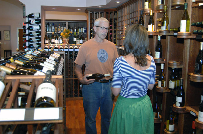 SOMETHING TO SAVOR: Jessica Granatiero, proprietor of the Savory Grape in East Greenwhich chats with longtime customer Paul Beaudette. The store uses loyalty programs to help build a relationship with customers. / PBN PHOTO/BRIAN MCDONALD