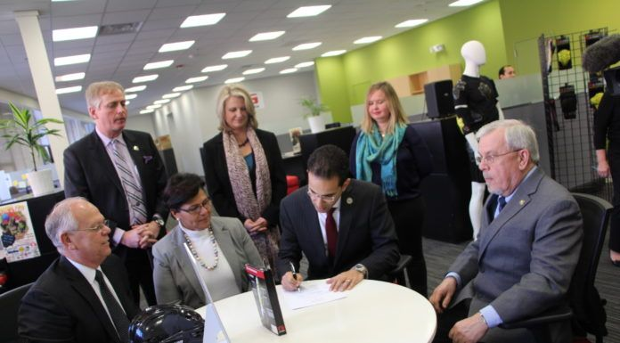 PROVIDENCE MAYOR ANGEL TAVERAS signs a new agreement with the U.S. Small Business Administration to facilitate assistance on a range of topics to enterprises based in the city. Under terms of the previous agreement, which began in May 2012, the SBA, the Center for Women and Enterprise, and SCORE engaged about 150 business owners in 12 workshops. Attending the signing event at Providence's G-form LLC, are, seated from left, Mark S. Hayward, director of the SBA's Rhode Island office, Carmen Diaz-Jusino, program manager for the Center for Women and Enterprise, Taveras, and George Hemond, chair of the Joseph G.E. Knight SCORE chapter. Standing, from left, are James Bennett, Providence director of economic development, Laurie White, president of the Greater Rhode Island Chamber of Commerce, and Meghan Downing, assistant to the CEO at G-Form. / COURTESY PROVIDENCE MAYOR'S OFFICE