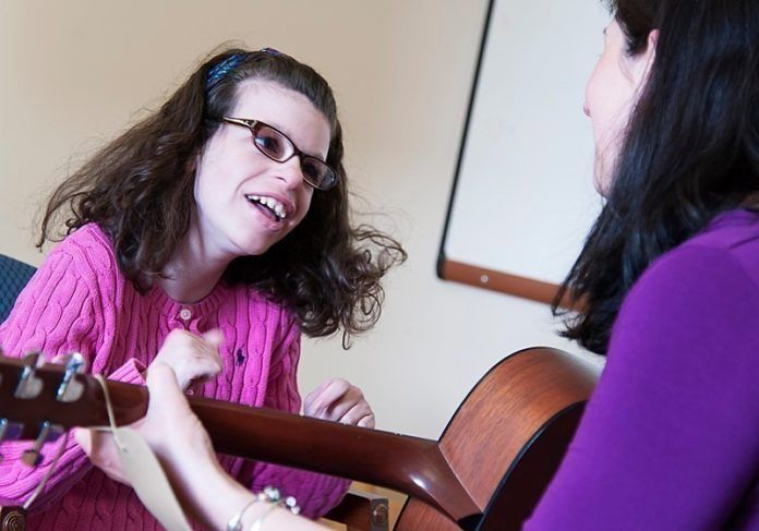 SWEET SOUNDS: Music therapist Nicole O'Malley works with client Maddie Manglass, a teenager who has been receiving music-therapy services for nearly 10 years. / PBN PHOTO/MICHAEL SALERNO