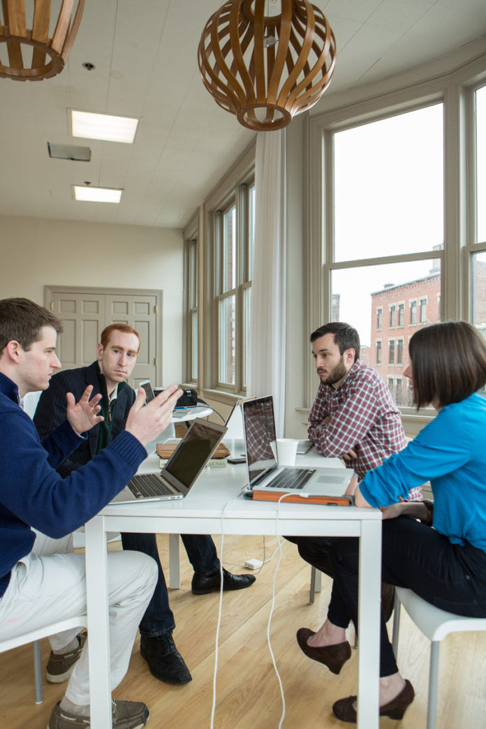 From left to right, CallRed co-founder Daniel Reilly and founder and CEO Andrew Kelley sit with Adam Croft and Sarah Cowan Johnson, of Intervarsity. / PBN PHOTO/RUPERT WHITELEY