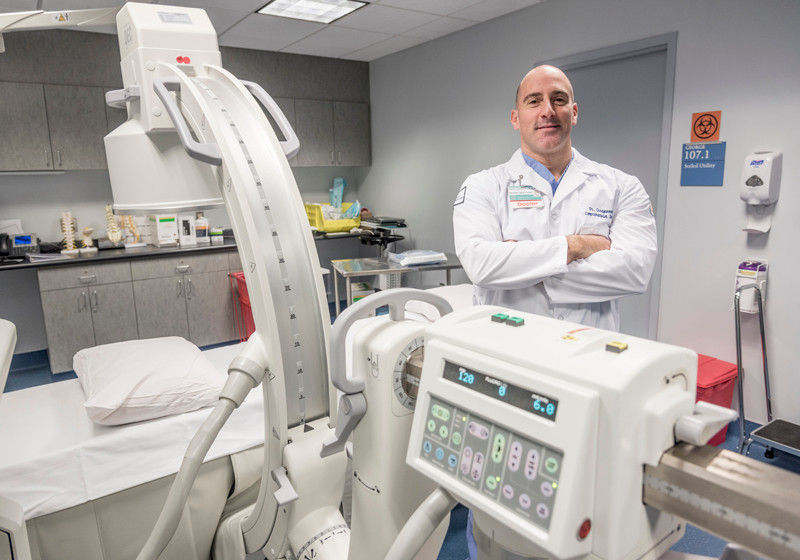 HELP FOR PAIN: Dr. Alexios Carayannopoulos, director of the new Comprehensive Spine Center at Rhode Island Hospital,  displays diagnostic equipment at the Lifespan facility. / PBN PHOTO/ MICHAEL SALERNO