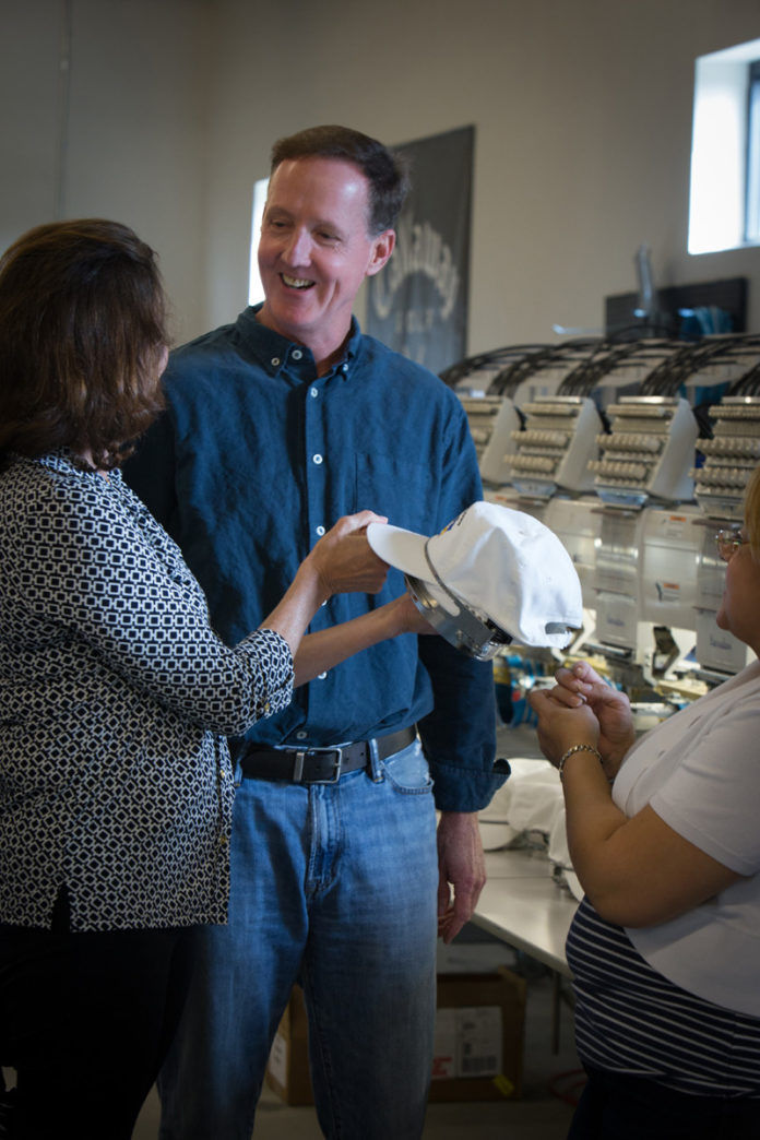 GOOD FIT: Thomas Parsons Kellogg III and his wife, Leslie, look at one of Parsons-Kellogg LLC's embroidered hats. / PBN FILE PHOTO/STEPHANIE ALVAREZ EWENS
