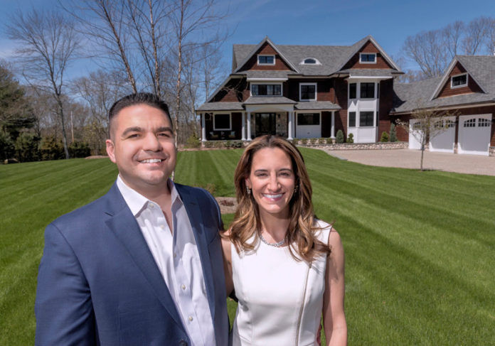 FORM AND FUNCTION: Jennifer and Gary Mello, owners of Seekonk-based The Mello Group, are seen in front of a home that Gary Mello designed. The 4,000-square-foot home has a large, open living area, a 12-foot island in the kitchen and a two-sided, two-story chimney with a fireplace both inside and out. / PBN PHOTO/MICHAEL SALERNO