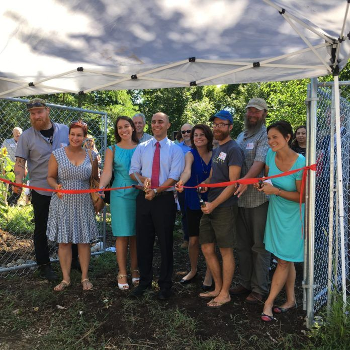 FROM LEFT TO RIGHT, Southside Community Land Trust Community Growers Director Rob Booz; Tina Shepherd of ONE Neighborhood Builders; Diana Perdomo of United Way of Rhode Island; Ken Ayers of R.I. Department of Environmental Managament; Providence Mayor Jorge O. Elorza; Terry Sullivan of the Nature Conservancy, Mia Patriarca of the R.I. Department of Health; Sky Hill Farmer Adam Graffunder; Scott Comings of the Nature Conservancy; and SCLT's Executive Director Margaret DeVos attend the ribbon cutting ceremony Wednesday morning celebrating the newly renovated Sky Hill Farm on Amherst Avenue in Providence. / COURTESY SOUTHSIDE COMMUNITY LAND TRUST
